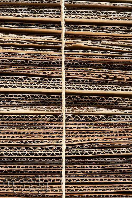 Bundle of corrugated cardboard tied with string close-up full frame