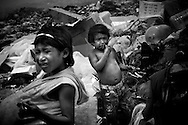 The children of Raisa Beria, 25, eat discarded chicken found in trash bags from a local fast food chain at the Cambalache dump in Ciudad Guayana, in northeastern Venezuela. In an effort to escape poverty, hunger and to be closer to health care facilities, approximately 300 Warao indigenous persons from the Delta Amacuro have settled in Ciudad Guayana. The Warao sustain themselves and their families by salvaging recyclables, clothing and discarded food in Cambalache, located minutes from downtown Ciudad Guayana. Although Warao community leaders say their quality of life is improved in comparison to the conditions in the Delta, the Warao are still plagued by hunger and diseases consequential of the unsanitary conditions of living and working in Cambalache.