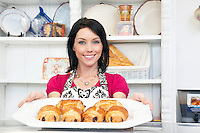 Portrait of a happy mid adult woman holding pastry tray in cake shop