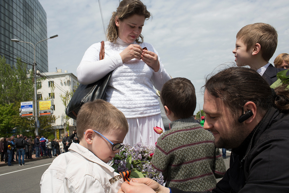 DONETSK, UKRAINE - MAY 9: A family pins St. George's ribbons, a common symbol of commemoration for World War II, on their children's shirts at a pro-Russia demonstration on May 9, 2014 in Donetsk, Ukraine. Tensions in Eastern Ukraine are high after pro-Russian activists seized control of at least ten cities and ahead of the Victory Day holiday and a planned referendum on greater autonomy for the region. (Photo by Brendan Hoffman/Getty Images) *** Local Caption ***