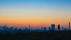 London, December 12 2017. A lone figure is seen against the skyline before the sun rises on a clear very cold morning in London, seen from Primrose Hill in Camden. © Paul Davey