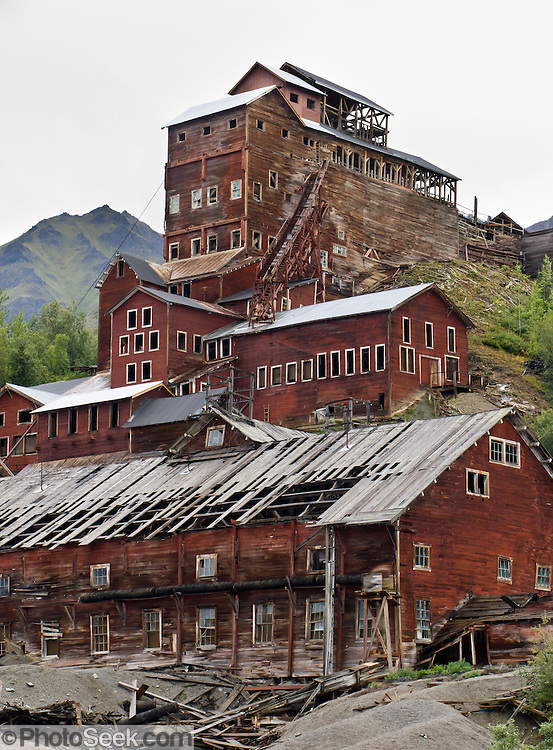 "Kennecott Concentration Mill rises 14 stories tall beneath Bonanza Ridge in the Wrangell Mountains, Alaska, USA. Kennecott Mines National Historic Landmark and nearby McCarthy lie within Wrangell-St. Elias National Park and Preserve, the largest National Park in the USA. Old mine buildings, artifacts, and colorful history attract summer visitors. Remote McCarthy is connected to Chitina via the McCarthy Road spur of the Edgerton Highway. At the east end of McCarthy Road, visitors must park their vehicle and walk across the footbridge to McCarthy. From McCarthy, a privately-operated shuttle takes visitors 5 miles to Kennecott. After copper was discovered between the Kennicott Glacier and McCarthy Creek in 1900, the Kennecott town, mines, and Kennecott Mining Company were created and named after the adjacent glacier. Kennicott Glacier and River had previously been named after Robert Kennicott, a naturalist who explored in Alaska in the mid-1800s. The corporation and town stuck with a mistaken spelling of ""Kennecott"" with an e (instead of ""Kennicott"" with an i). Partly because alcoholic beverages and prostitution were forbidden in the company town of Kennecott, the neighboring town of McCarthy grew quickly to provide a bar, brothel, gymnasium, hospital, and school. The Copper River and Northwestern Railway reached McCarthy in 1911 to haul over 200 million dollars worth of ore 196 miles to the port of Cordova on Prince William Sound. By 1938, the worlds richest concentration of copper ore was mostly gone, the town was mostly abandoned, and railroad service ended. Not until the 1970s did the area began to draw young people for adventure and the big money of the Trans Alaska Pipeline project. Declaration of Wrangell-St. Elias National Park in 1980 drew adventurous tourists who helped revive McCarthy with demand for needed services. Wrangell-St. Elias National Park and Preserve is honored by UNESCO as part of an International Biosphere Reserve and UNESCO World Heritage"