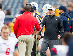 Sep 12, 2015; Morgantown, WV, USA; West Virginia Mountaineers head coach Dana Holgorsen talks with Liberty Flames head coach Turner Gill before the start of their game at Milan Puskar Stadium. Mandatory Credit: Ben Queen-USA TODAY Sports