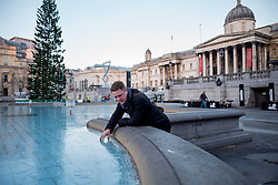 © Licensed to London News Pictures. 12/12/2017. London, UK. Commuters react to frozen water fountains in Trafalgar Square, London as temperatures drop bellow -3C across the capital overnight on Tuesday, 12 December 2017. Photo credit: Tolga Akmen/LNP