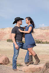 girl standing on a rock to get a better view of her cowboy