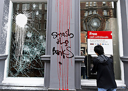 © under license to London News Pictures. 26/03/2011. A young man uses a Cash Dispenser at the recently attacked HSBC In Shaftsbury Avenue. The bank was attacked during The March for the Alternative in London on Sat 26th March. Picture credit should read: Julie Edwards/London News Pictures