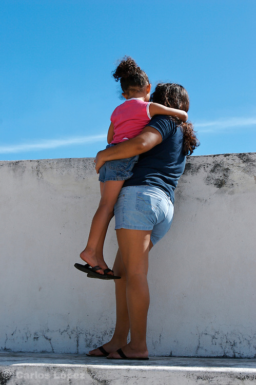 A mother is hanging her daughter, so she will be able to see what's is going on in the other side.