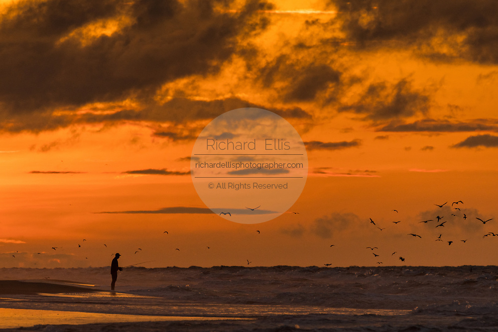 A fisherman casts his line on the beach at sunrise on a cloudy morning June 5, 2017 in Folly Beach, South Carolina. Folly Beach is a quirky beach community outside Charleston known to locals as the Edge of America.
