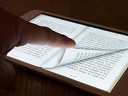 Turning page of an e book with an  iBook reader on an iPad mini tablet computer