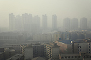 The whole town of Lanzhou is overlaid by a visible lay of pollution from automobile traffic and factories activity using coal. Here housings in the centertown. <br /> <br /> -------<br /> Lanzhou, in the Gansu province is the most polluted cities of China and in the world's top ten for atmospheric pollution due to human activity. The town is situated between two hills along the Yellow River and the polluted clouds remain blocked over the town. The sky is most of the time hidden by the pollution.