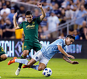 Sporting Kansas City midfielder Felipe Gutierrez (21) gets tripped up by Portland Timbers midfielder Andres Flores (14) during the second half of an MLS soccer match in Kansas City, Kan., Saturday, Aug. 18, 2018. Sporting beat the Timbers 3-0. (AP Photo/Colin E. Braley)