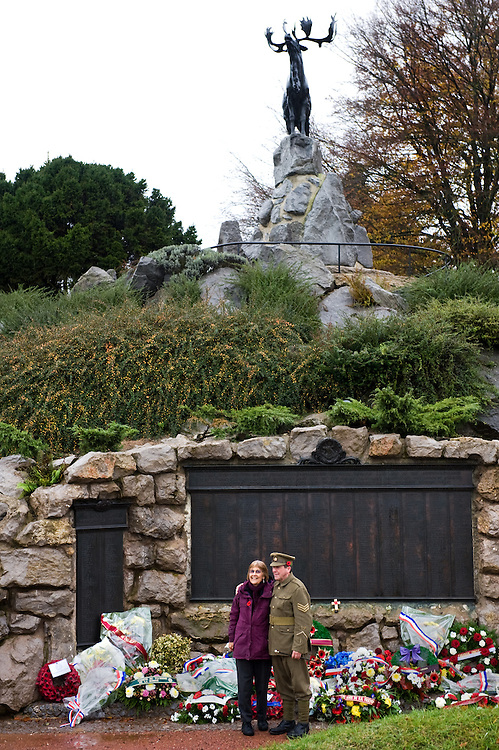 A man dressed with a ‪Canadian Expeditionary Force‬  officers uniform poses for a photograph with a tourist  in front of the Beaumont-Hamel Newfoundland Memorial. On the back are the three bronze tablets that carry the names of 820 members of the Royal Newfoundland Regiment, the Newfoundland Royal Naval Reserve, and the Mercantile Marines who died in the First World War and have no known grave. The Caribou Memorial, the emblem of the Royal Newfoundland Regiment, standing atop a mound of Newfoundland granite. Beaumont-Hamel Newfoundland Memorial is dedicated to the commemoration of the Newfoundland Regiment that fought in the battle of Somme and WWI in general. Most of the  Newfoundland Regiment were dead within 15 to 20 minutes of leaving their trench in the morning of the 1st July 1916 during the first day of the Battle of the Somme.