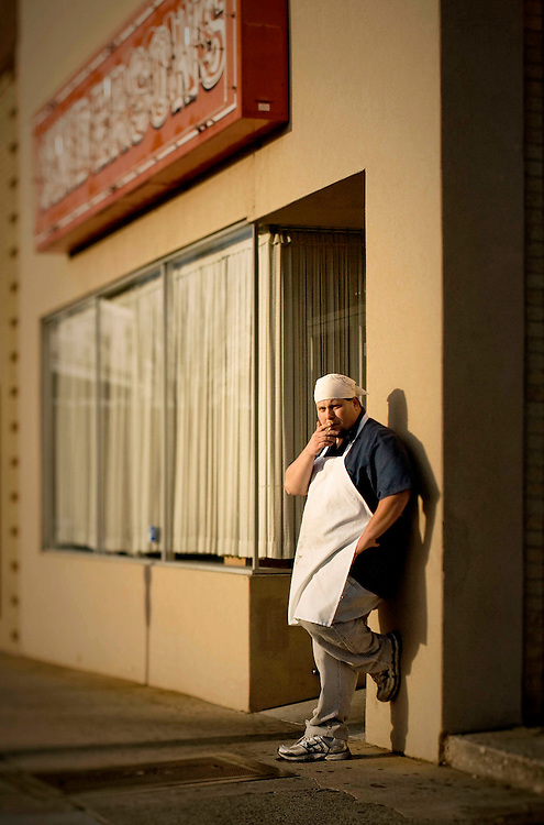 An image of a restaurant cook taking a cigarette break outside. of Anderson's Restaurant in Charlotte, North Carolina.