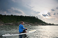 A female stand up paddler sits on her board and rests while paddling on Lake Superior near Marquette Michigan.