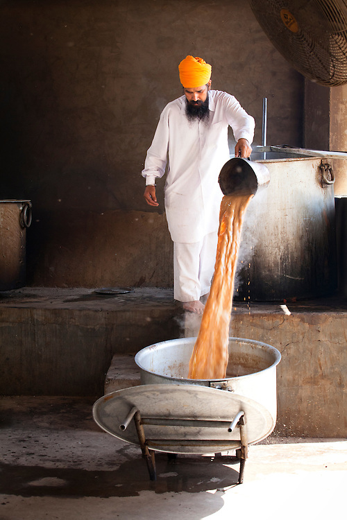 A Sikh cook pours hot chai to a smaller pot for distribution in the Sikh kitchen. Food and chai are provided for free to all visitors of the Sikh temple.