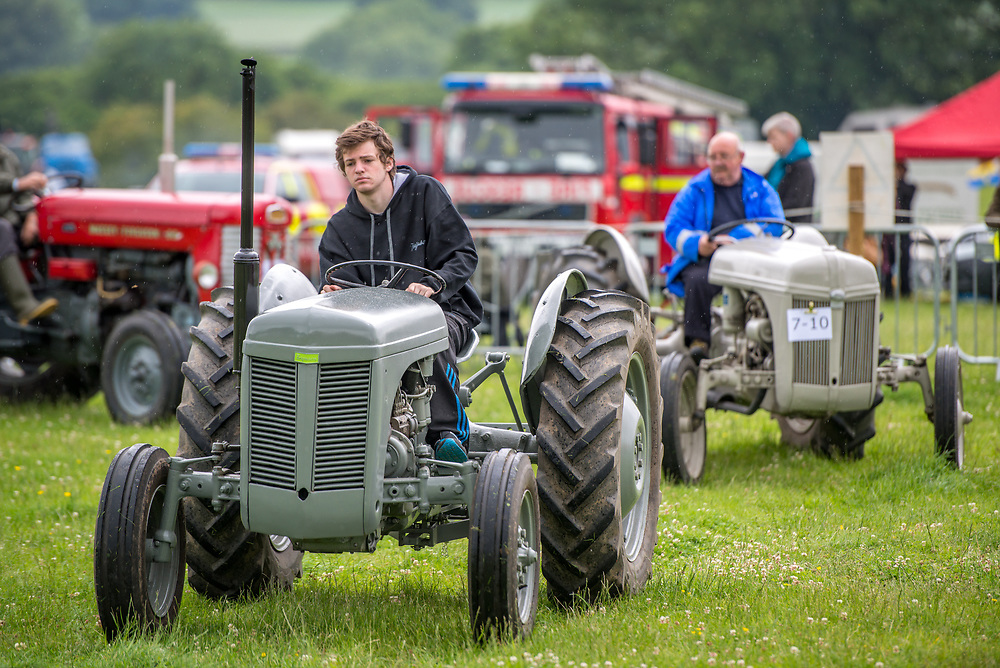 Teenage boy operates vintage tractor with mature male following closely behind on his own vintage tractor, Masham, North Yorkshire, UK