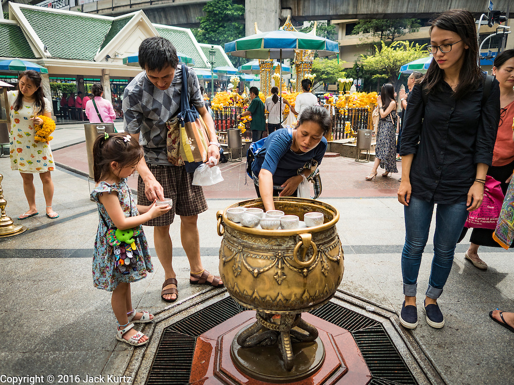 16 AUGUST 2016 - BANGKOK, THAILAND:  A man sprinkles holy water on his daughter at Erawan Shrine one year after the shrine was bombed in the worst international terrorist attack in Thai history. On 17 August 2015, a bomb was set off at the Erawan Shrine, a popular tourist attraction and important religious shrine in the heart of the Bangkok shopping district. According to the Royal Thai Police  20 people were killed in the bombing and 125 injured. Thai Police arrested an alleged Uighur extremist for the bombing. The case against him is still pending in Thai courts. The shrine was repaired, rededicated and reopened to the public on 4 September 2015.      PHOTO BY JACK KURTZ