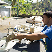 OCTOBER 25 - UTUADO, PUERTO RICO - <br /> Edwin Natal Maldonado, 27, fills up cisterns with potable water at a station next to the Lago Dos Bocas in Utuado. Troops from Fort Bragg, NC, are using a water filtration system to purify the brownish liquid.<br /> (Photo by Angel Valentin/Freelance)