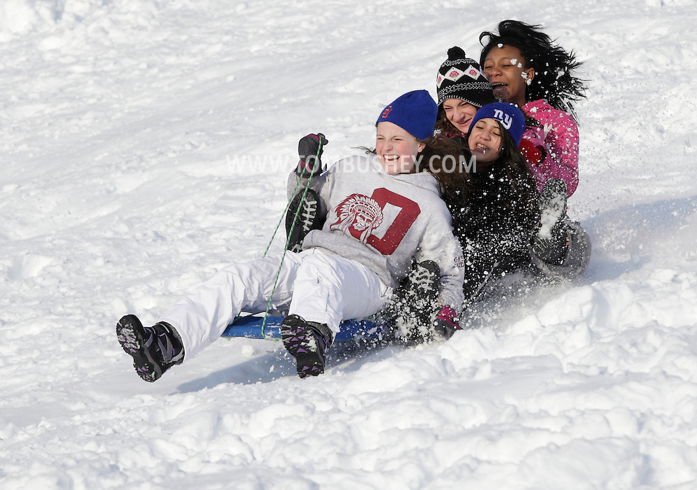 Central Valley, NY - Four teenage girls slide down a hill next to the Central Valley Elementary School after a snow storm on  Feb. 27, 2010.