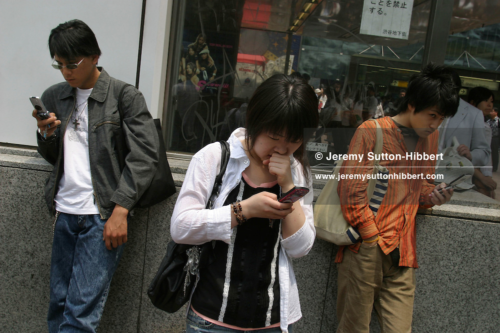 Young people using their mobile phones. Phones in Japan are heavily used for text messaging, internet, reading novels, and for cashless money paying functions.  Shibuya, Tokyo, Japan.