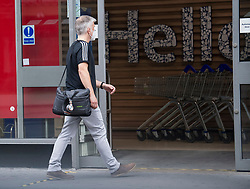 © Licensed to London News Pictures. 24/07/2020. London, UK. A shopper enters Tesco on Goodge Street in central London wearing a face mask, on the day that the wearing of mask in shops becomes compulsory. The UK Government has published formal guidance on spaces where the wearing of masks will now be mandatory, including in shops, supermarkets and shopping centres. Photo credit: Ben Cawthra/LNP