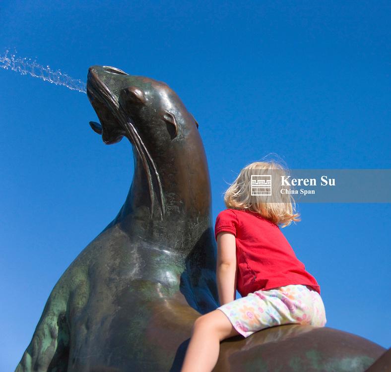 Child riding on statue in Esplanade Park, Helsinki, Finland
