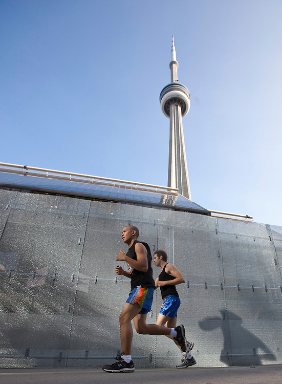 Runners jog past the security fences in downtown Toronto, Canada June 24, 2010. The fences surround the Toronto convention center which will be hosting the G20 summit this weekend.<br /> AFP/GEOFF ROBINS/STR
