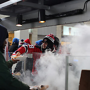 Fans queue for food on a bitterly cold day at Yankee Stadium during the New York Rangers Vs New Jersey Devils NHL regular season game held outdoors at Yankee Stadium, The Bronx, New York, USA. 26th January 2014. Photo Tim Clayton