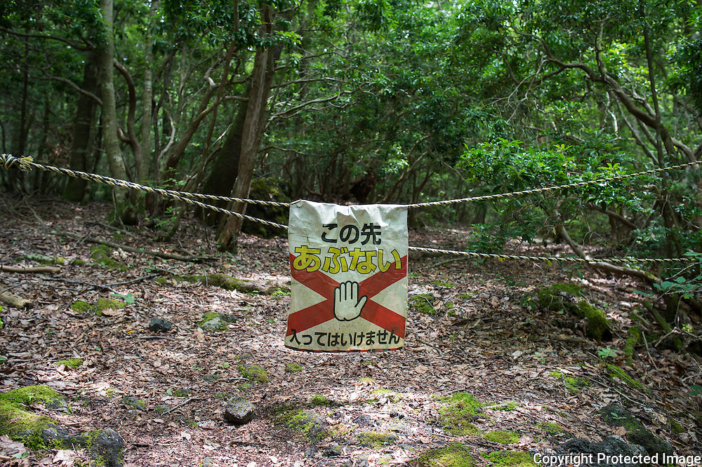 A sign warning people of danger ahea in Aokigahara Jukai, better known as the Mt. Fuji suicide forest