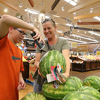 """Aiden Harris, 12, helps his mother, Monte, scan items as they shop with the new """"scan and go"""" at the Kroger location at crosstown in Tupelo."""