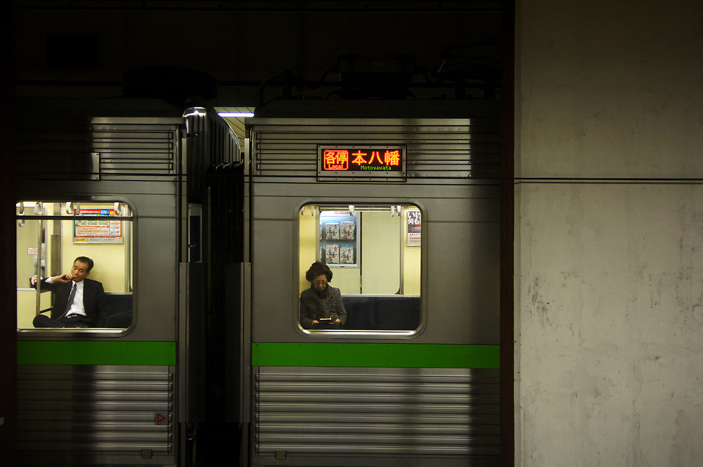 Passengers on an underground train at the extremely busy and complex Shinjuku station in Tokyo.