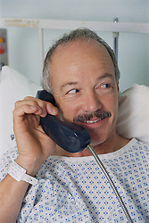 Patient recently back from hand surgery sitting in hospital bed using telephone,