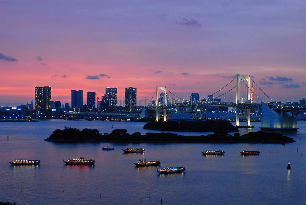"""With Rainbow Bridge and the,  downtown city skyline in the background""""Yakata-bune"""" pleasure boats set anchor on the placid waters of the Daiba area of Tokyo Bay in Tokyo, Japan on 3 Sept.  2010. .Photographer: Rob Gilhooly"""