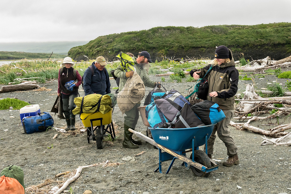 Ranger Tom Griffin, center, helps newly arrived campers carry their gear along the sandy spit to the camp ground at the remote McNeil River Game Sanctuary in the Katmai Peninsula, Alaska. The remote park has the largest concentration of brown bears in the world.