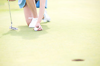 Low section of woman placing ball at golf course