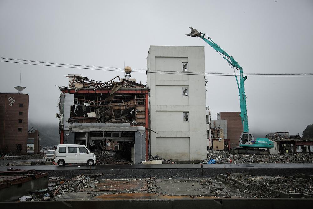 Onagawa - travaux de d&eacute;molition - juin 2011<br /> Du front de mer au fond de la vall&eacute;e, les ravages du tsunami sont tels que rien ne pourra &ecirc;tre pr&eacute;serv&eacute;. Ce b&acirc;timent de quatre &eacute;tages fut submerg&eacute; et, comme tous les autres encore debout, il sera d&eacute;truit. Au fond de la vall&eacute;e, dans une ancienne zone r&eacute;sidentielle, s'amonc&egrave;le des tonnes de tout ce qui fut d&eacute;truit. Les d&eacute;bris sont agglom&eacute;r&eacute;s par cat&eacute;gories de bois, dacier, de b&eacute;ton ou de mati&egrave;res diverses afin que dans la mesure du possible, une majorit&eacute; des mat&eacute;riaux soit recycl&eacute;s.
