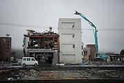Onagawa - travaux de démolition - juin 2011<br /> Du front de mer au fond de la vallée, les ravages du tsunami sont tels que rien ne pourra être préservé. Ce bâtiment de quatre étages fut submergé et, comme tous les autres encore debout, il sera détruit. Au fond de la vallée, dans une ancienne zone résidentielle, s'amoncèle des tonnes de tout ce qui fut détruit. Les débris sont agglomérés par catégories de bois, dacier, de béton ou de matières diverses afin que dans la mesure du possible, une majorité des matériaux soit recyclés.