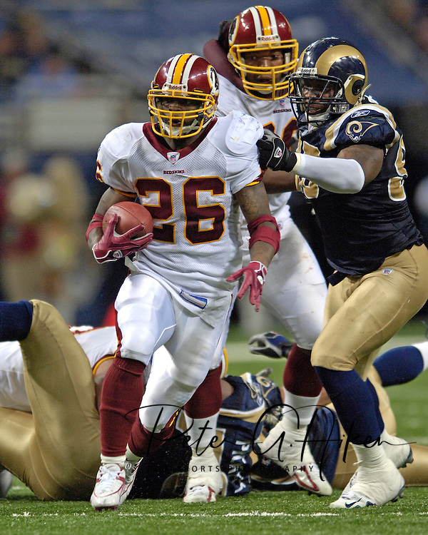 Washington Redskins running back Clinton Portis (26) rushes up the middle past St. Louis Rams defensive end Demetric Evans (R) in the fourth quarter, during the Redskins 24-9 win at the Edward Jones Dome in St. Louis, Missouri, December 4, 2005.