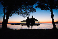 A man and a woman sitting on a bench at County Park, San Juan Island watching the sun set over Haro Strait and the Gulf Islands of British Columbia.  Washington, USA.