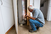 Mike Lehman from the Coporation for Appalachian Development (COAD) inspects the hot water tank at 86 West State Street during an energy audit on Wednesday, June 24, 2015.  Photo by Ohio University  /  Rob Hardin