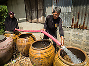 14 JULY 2015 - THAILAND:  A provincial water department worker (right) delivers water to a homeowner (left) in Nakhon Nayok province. The drought that has crippled agriculture in central Thailand is now impacting residential areas near Bangkok. The Thai government is reporting that more than 250,000 homes in the provinces surrounding Bangkok have had their domestic water cut because the canals that supply water to local treatment plants were too low to feed the plants. Local government agencies and the Thai army are trucking water to impacted communities and homes. Roads in the area have started collapsing because of subsidence caused by the retreating waters. Central Thailand is contending with drought. By one estimate, about 80 percent of Thailand's agricultural land is in drought like conditions and farmers have been told to stop planting new acreage of rice, the area's principal cash crop.      PHOTO BY JACK KURTZ