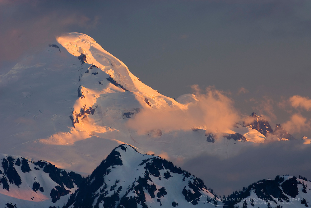 Mount Baker (elevation 10,778feet (3,285m) seen through clearing storm clouds at sunset, North Cascades Washington USA