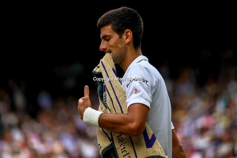 LONDON, ENGLAND - JULY 6: Novak Djokovic of Serbia bites the towel during the Gentlemens' Singles final match against Roger Federer of Switzerland on day thirteen of the Wimbledon Lawn Tennis Championships at the All England Lawn Tennis and Croquet Club at Wimbledon on July 6, 2014 in London, England.