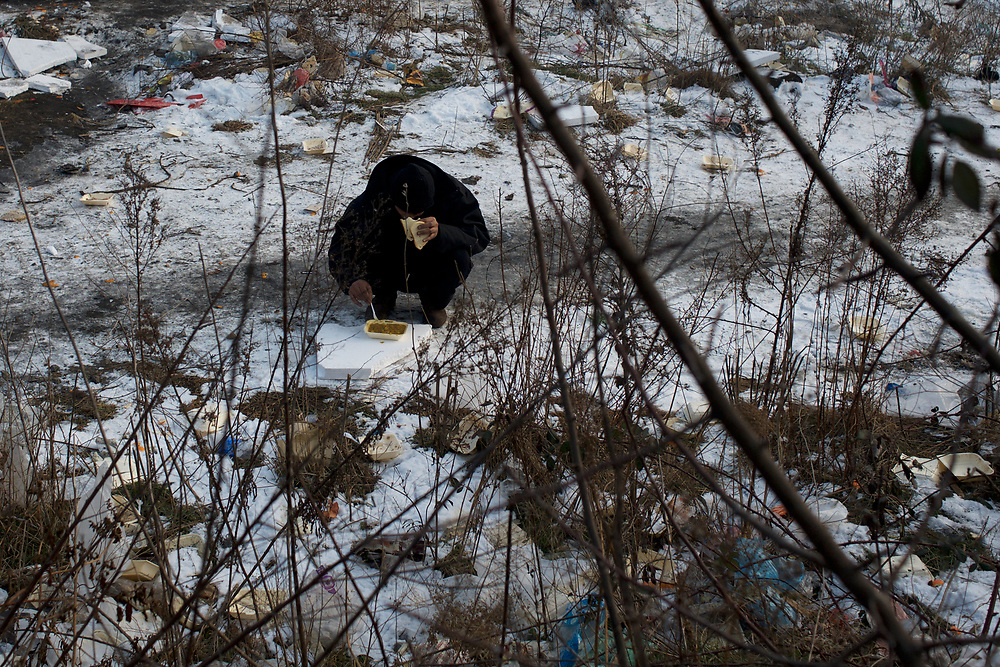 A migrant eats his meal in the frozen ground outside the old warehouses near Belgrade's main railway station. Volunteer groups provide a daily meal to the thousands of refugees living here. For the majority, this is the only daily meal they have access to.