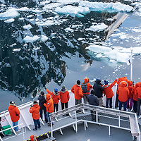 Guests on the bow of the National Geographic Explorer observe the stunning landscape as the ship passes through the glassy reflections of the Lemaire Channel in Antarctica.