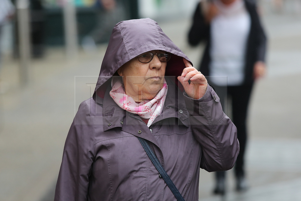 © Licensed to London News Pictures. 22/08/2016. Leeds, UK. A woman wearing a winter coat on a rainy and windy day in Leeds, West Yorkshire. Forecaster are predicting a heatwave this week, but it has started with rain, wind and no sunshine. Photo credit : Ian Hinchliffe/LNP
