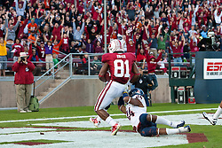 November 6, 2010; Stanford, CA, USA;  Stanford Cardinal wide receiver Chris Owusu (81) scores a touchdown past Arizona Wildcats cornerback Trevin Wade (24) during the first quarter at Stanford Stadium.