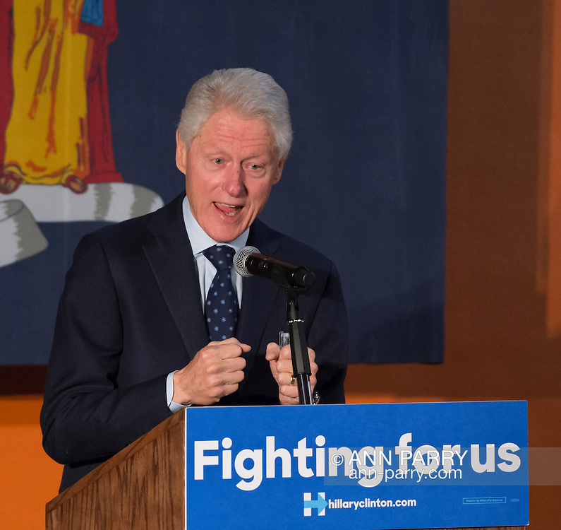 Elmont, New York, USA. April 5, 2016. Former President Bill Clinton, clenching his two hands into fists while giving a speech, is the headline speaker as he campaigns at an Organizing Event rally in Elmont, Long Island, on behalf of his wife, Hillary Clinton, the leading Democratic presidential candidate, and former Secretary of State and U.S. Senator for New York. Podium has 'Fighting for us' slogan on sign. The New York Democratic Primary takes place April 19th.