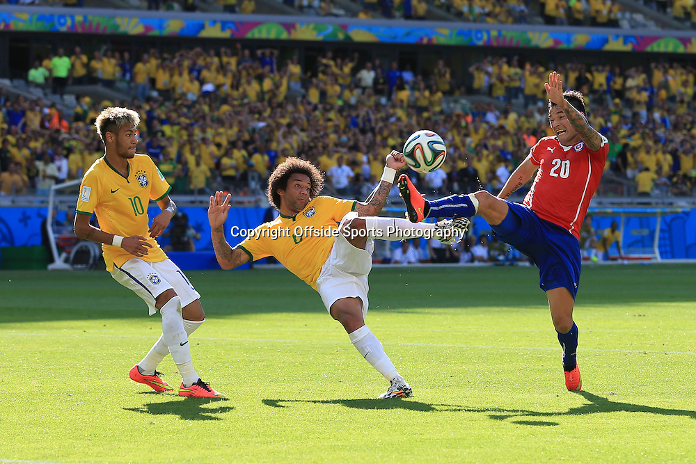 28th June 2014 - FIFA World Cup - Round of 16 - Brazil v Chile - Charles Aranguiz of Chile challenges Marcelo of Brazil - Photo: Simon Stacpoole / Offside.