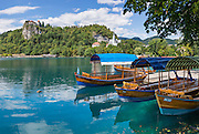 "Pletna boats carry tourists across Lake Bled under the medieval Bled Castle (Slovene: Blejski grad, German: Burg Veldes), which was built a little before 1011 AD on a cliff above the city of Bled, in what is now Slovenia, Europe. The distinctive two-paddle Pletna boats originated in 1590 and can carry 20 people. A colourful awning protects passengers from sun and weather. The respected title of ""Pletnarstvo,"" Pletna oarsman, has been handed down within specific families from generation to generation. This panorama was stitched from 4 overlapping photos."